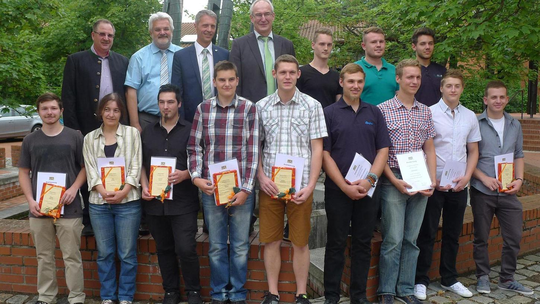 Schulleiter Michael Greiner (hinten Mitte) sowie die Gäste aus Politik und Handwerk verabschiedeten die Berufsschüler. Die Besten gingen nicht ohne Geschenke und Preise nach Hause.