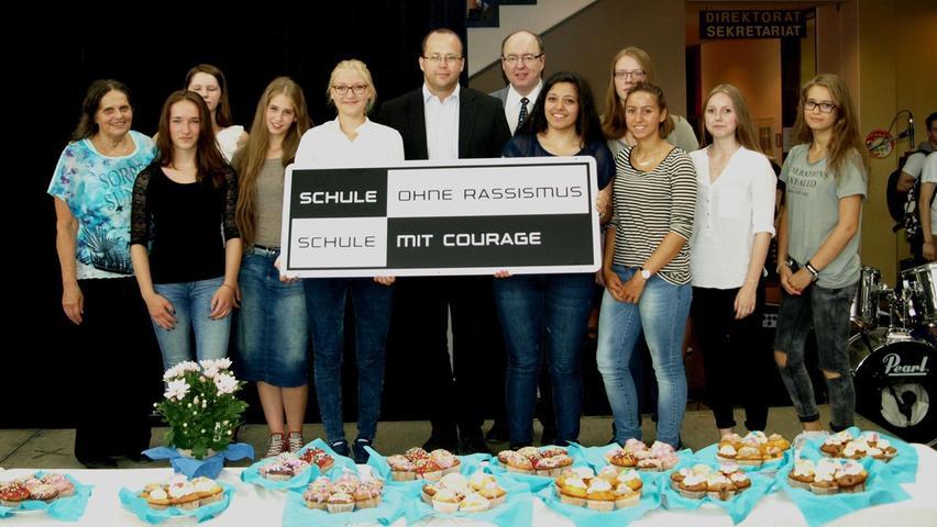 """Im Juli 2015 hat die Staatliche Realschule Schwabach den Titel """"Schule ohne Rassismus – Schule mit Courage"""" erhalten. Auf dem Foto sind neben den Schülerinnen der SMV auf der linken Seite Patin Brigitte Koller, in der Mitte Bertram Höfer und rechts neben ihm Norbert Mager zu sehen."""