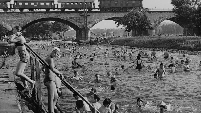 An heißen Tagen soll das Flussbad bis zu 12000 Badegäste angezogen haben. Ein Bild aus den 50ern mit Blick auf die Siebenbogenbrücke.