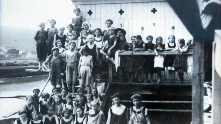 """Dieses Bild aus der Zeit um die Jahrhundertwende zeigt das erste Treuchtlinger """"Badehaus"""" direkt am Altmühlufer – und die aus heutiger Sicht kuriose """"Bademode"""" dieser Zeit. Männer und Frauen gemeinsam im Wasser und auf dem Foto? Damals undenkbar. Nach der Altmühlregulierung entstand 1911 die"""