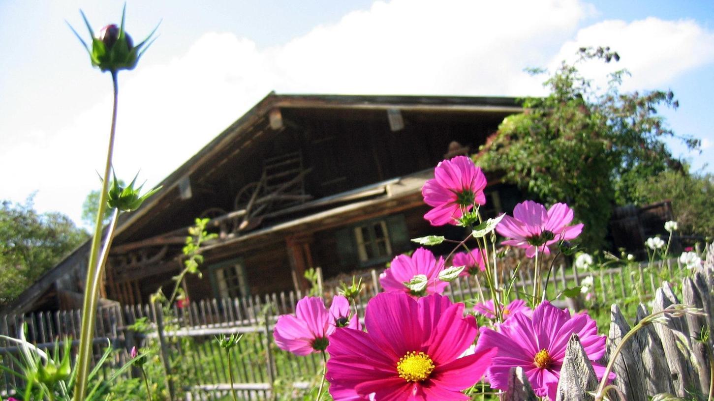 Ein Holzhaus mit Fensterläden, davor Blumen im eigenen Garten – nicht immer kann die ländliche Idylle halten, was sie verspricht.