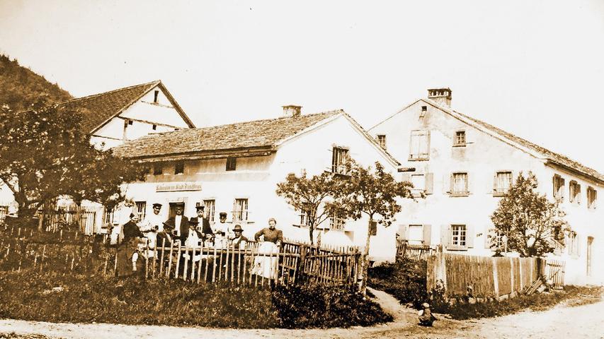Dieses Foto zeigt die ursprüngliche Wirtschaft in Gstadt, die in dieser Form bis zum Jahr 1905 betrieben wurde. Inhaber war Georg Meyer. Das Gebäude ist heute noch in Familienbesitz und wird als Wohnhaus genutzt. Links neben der Wirtschaft ist die dazugehörige Scheune zu sehen, rechts das Anwesen Jungmeyer. Der Bergrücken links im Hintergrund ist der Patrichberg. Mehr zu der Geschichte des Anwesens lesen Sie hier.