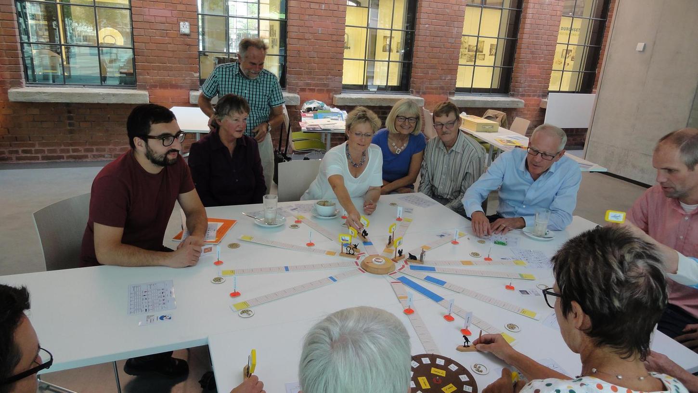 Die Bürgermeisterin Susanne Lender-Cassens ist am Zug, die übrigen Spielteilnehmer im Siemens MedMuseum schauen ihr gespannt zu.