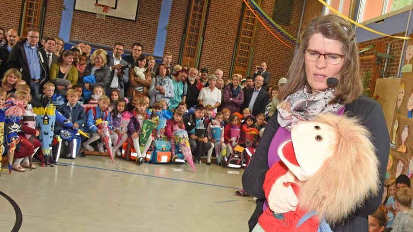 ... in der Turnhalle begrüßt. Rechts im Bild: Die neue Rektorin Ulrike Ringlein mit den Puppen Johannes und Flori.