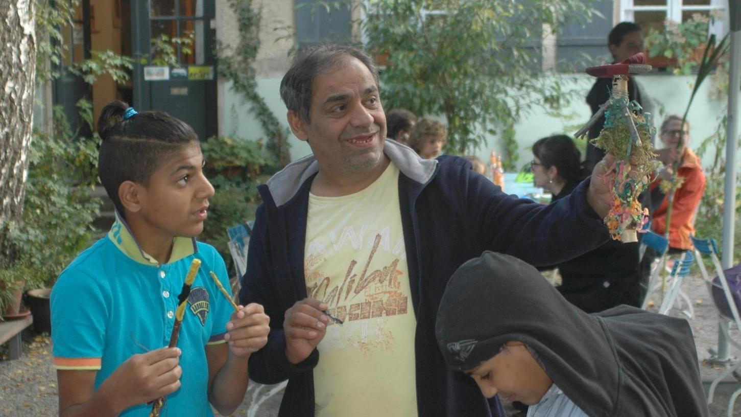 Begeistert hält ein Vater vor dem Kulturort Badstraße 8 eine von seinen Kindern aus einfachen Materialien gebastelte Puppe in die Höhe.