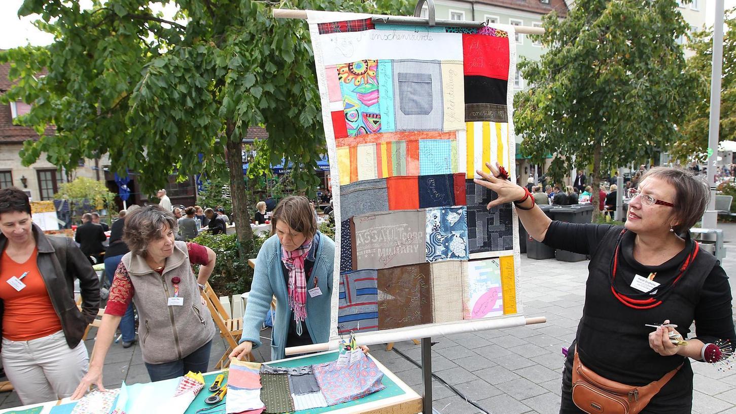 Einsatz für die Rechte von Textilarbeiterinnen: An Rand der Friedenstafel prangert die Künstlerin Heidi Drahota mit einer Nähaktion zum Mitmachen die Missstände an.