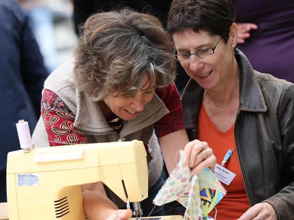 Besucherinnen verarbeiten ihre Stoffreste für ein geplantes Spenden-Kunstwerk.