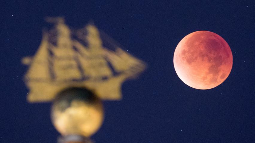 Der Mond erscheint am 28.09.2015 in Hamburg in rotem Licht neben dem Denkmal  eines Segelschiffes. Bei einer totalen Mondfinsternis durchläuft der Mond  vollständig den Kernschatten der Erde und erscheint dabei in rotem Licht. Foto:  Daniel Reinhardt/dpa +++(c) dpa - Bildfunk+++