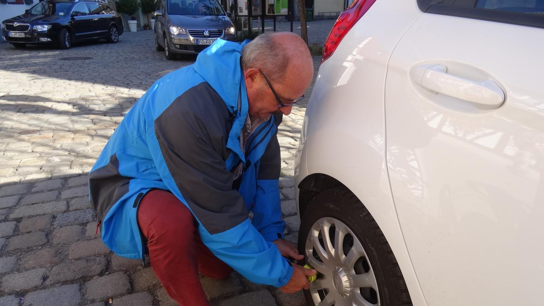 Ein städtischer Mitarbeiter montiert einen Ventilwächter zur Probe. Werden die Rückstände nicht innerhalb von drei Tagen bezahlt, wird das Auto kostenpflichtig abgeschleppt und später versteigert.
