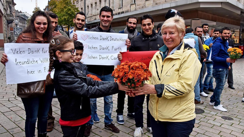Die achtjährige Qamar überreichte einen Strauß an eine Passantin in der Fußgängerzone. Die Erwachsenen hielten Schilder mit Dankesworten hoch.