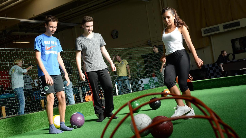 """Tim, Nico und Selina (von links) von der Leopold-Ullstein-Realschule in Fürth entdecken auf ihrem Wandertag im """"indoor Sport Fürth"""" die Sportart Fußball-Billard für sich."""