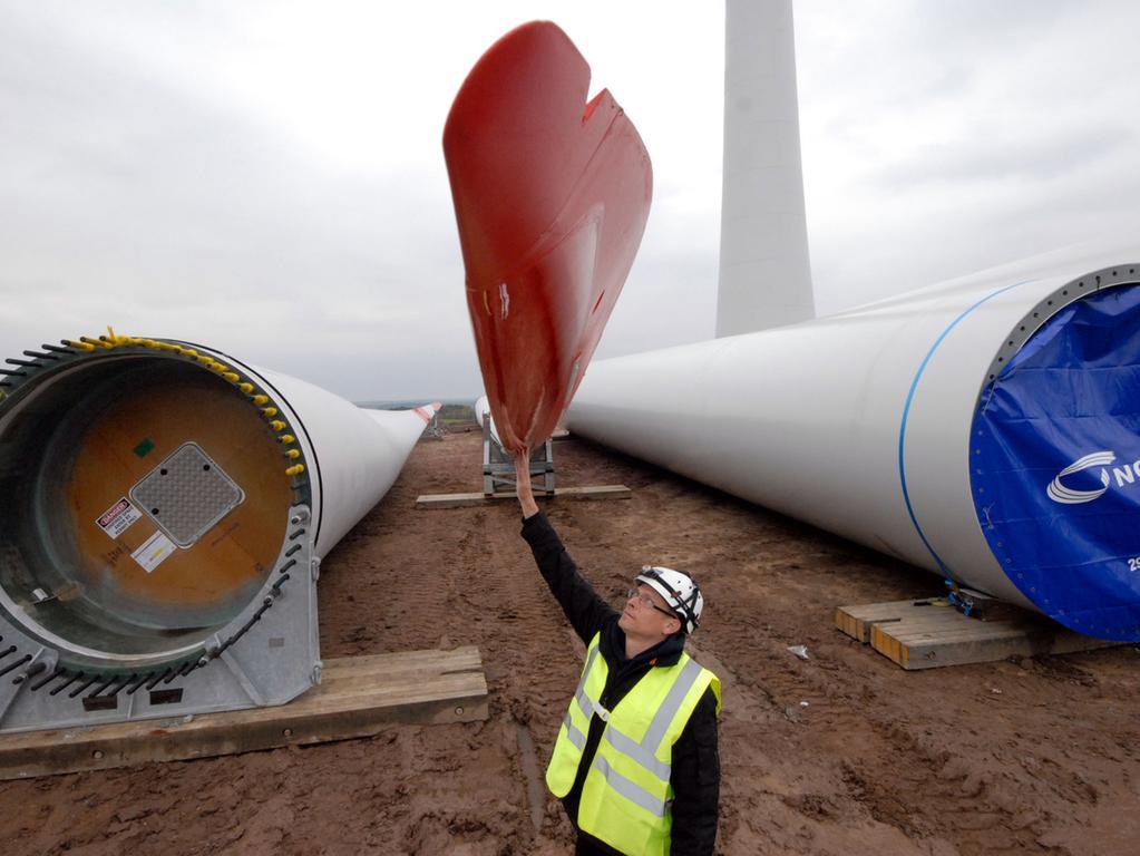 Windrad 4, Oktober: Bauleiter Hanno Jauken berührt eines der Rotorblätter. Rechts eines der  Turmelemente, die noch gesetzt werden müssen, damit die Nabenhöhe von rund 140  Meter erreicht wird.