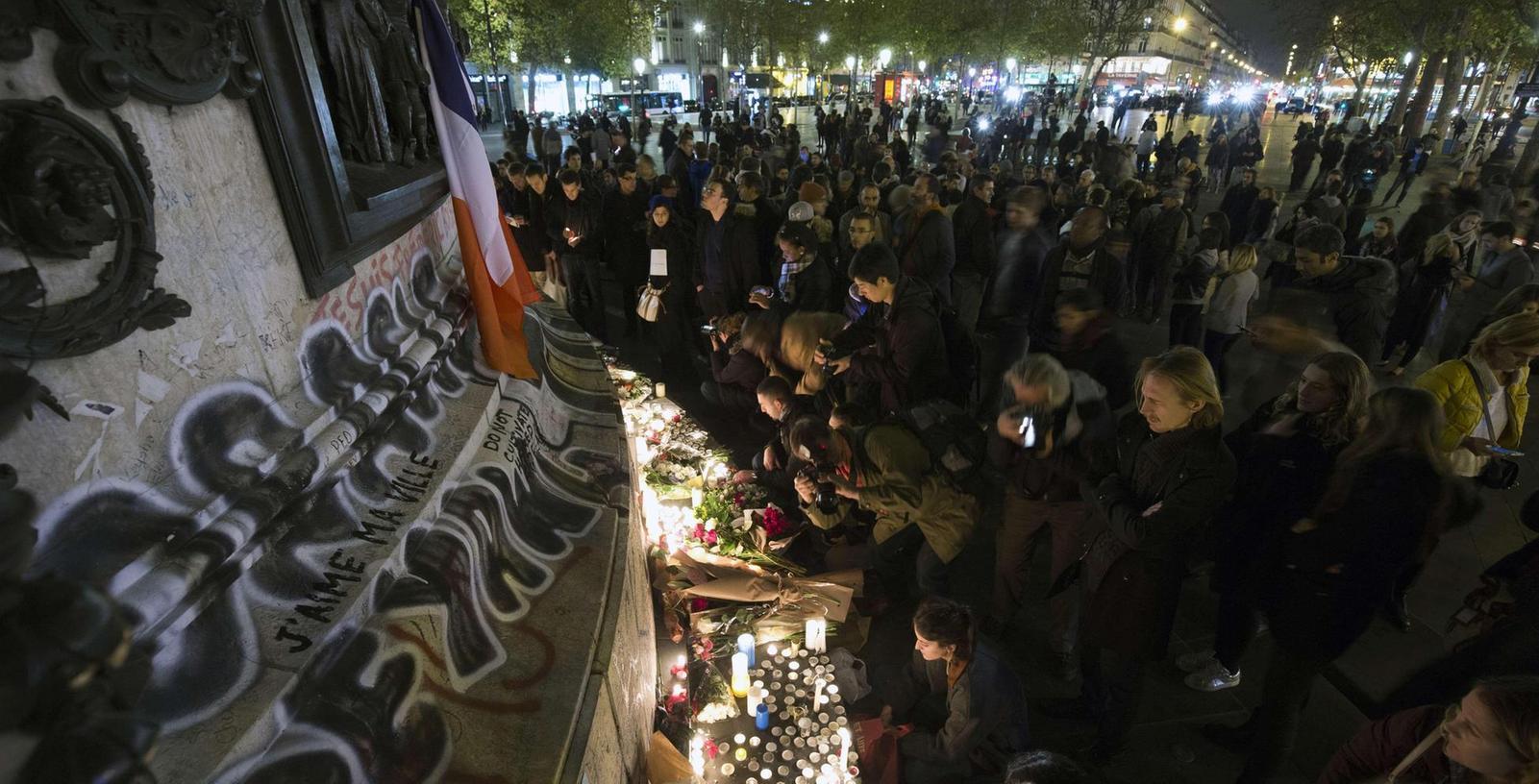 Zahlreiche Menschen stellen am Pariser Platz der Republik Kerzen auf und legen Blumen nieder, um ihrer Trauer Ausdruck zu verleihen.