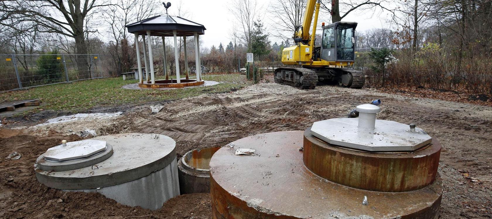 Auch der hier freigelegte Brunnenkopf muss vollständig erneuert werden. Im Hintergrund: der vom Bürgerverein Gebersdorf errichtete Quellpavillon. Rechts vom Bagger verläuft der Buckweg nach Weikershof.