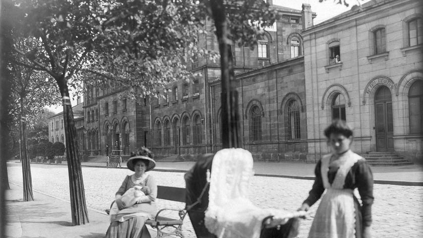 Die Frau des Bahnhofsvorstehers mit Enkelin und mit einem Kindermädchen vor dem Bahnhofsgebäude.