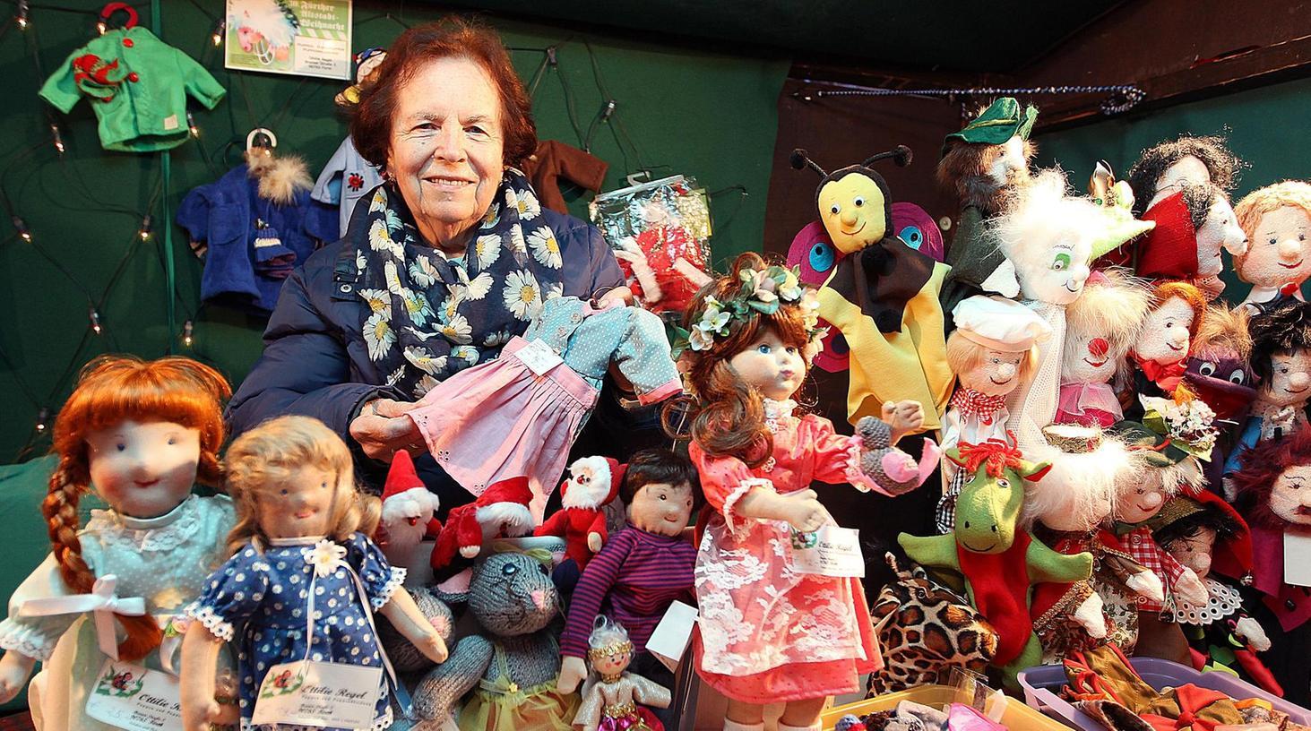 Inmitten ihrer Handarbeiten sitzt Ottilie Regel auf der Altstadtweihnacht und freut sich, wenn sie Kunden beim Einkleiden der Puppen helfen kann. Foto: Ralf Rödel