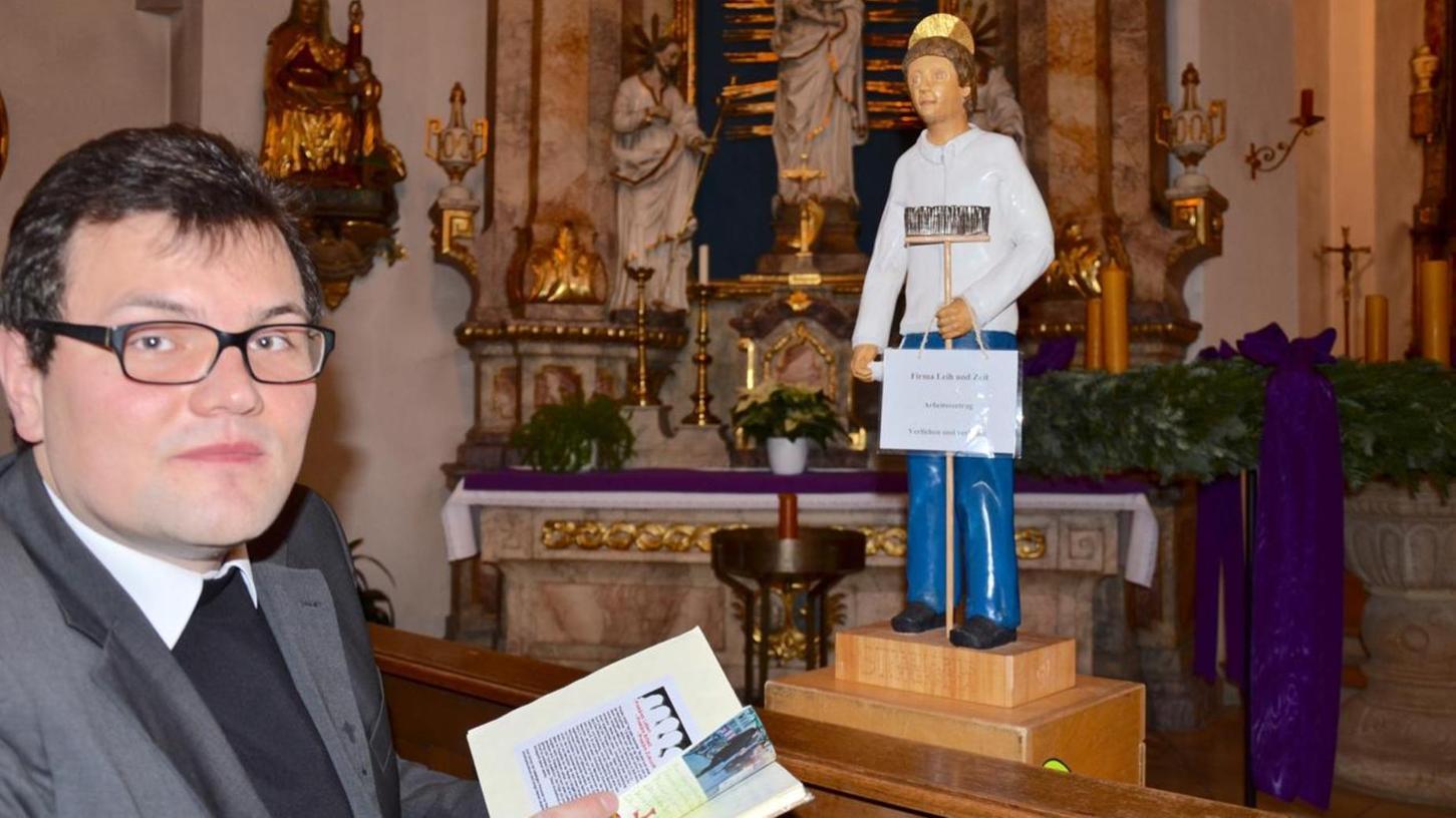 Pfarrer Florian Stark liest in den Dokumenten, die den heiligen Prekarius (Mitte) auf seinen Weg durch die bayerischen Diösesen begleiten. Der Holz-Heilige weist auf prekäre Arbeitsverhältnisse hin.