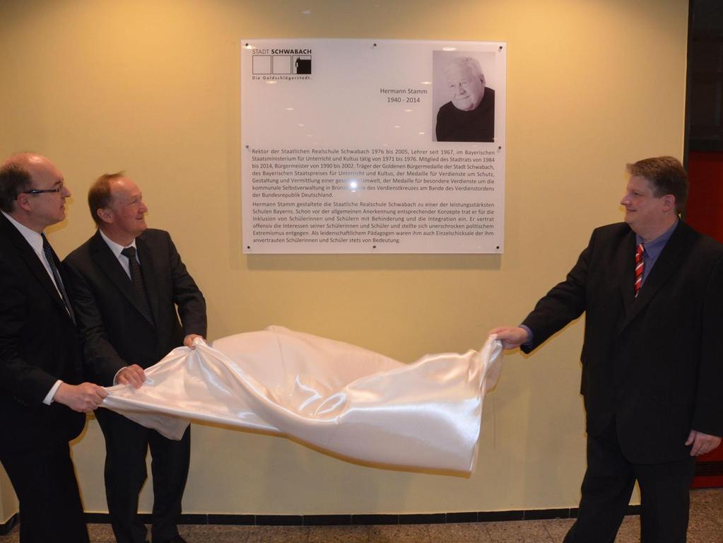 Hermann Stamms Sohn Markus (rechts) enthüllt zusammen mit Rektor Norbert Mager (links) und dem Ministerialbeauftragten Johann Seitz die Gedenktafel in der Aula.