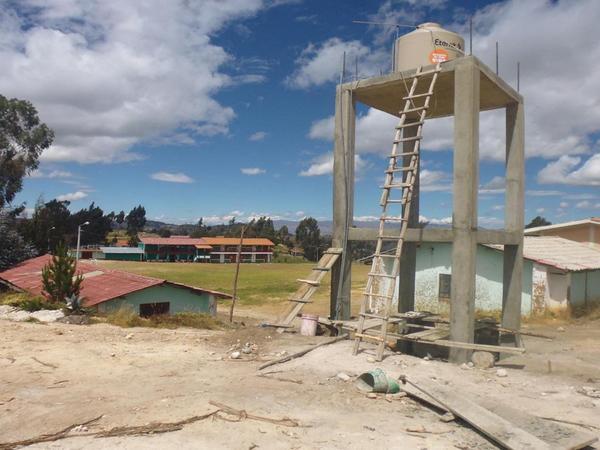Der noch nicht angeschlossene Wassertank, im Hintergrund die dreiklassige Primarschule.