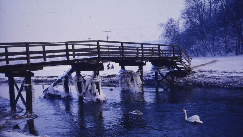 Das Foto zeigt den Altmühlsteg, wie er um 1975 aussah. Mittlerweile ist der Steg an selber Stelle erneuert und mit Rampen versehen, statt mit Stufen. Auf dem Stadtweiher im Hintergrund war im Winter immer viel Eislaufbetrieb.
