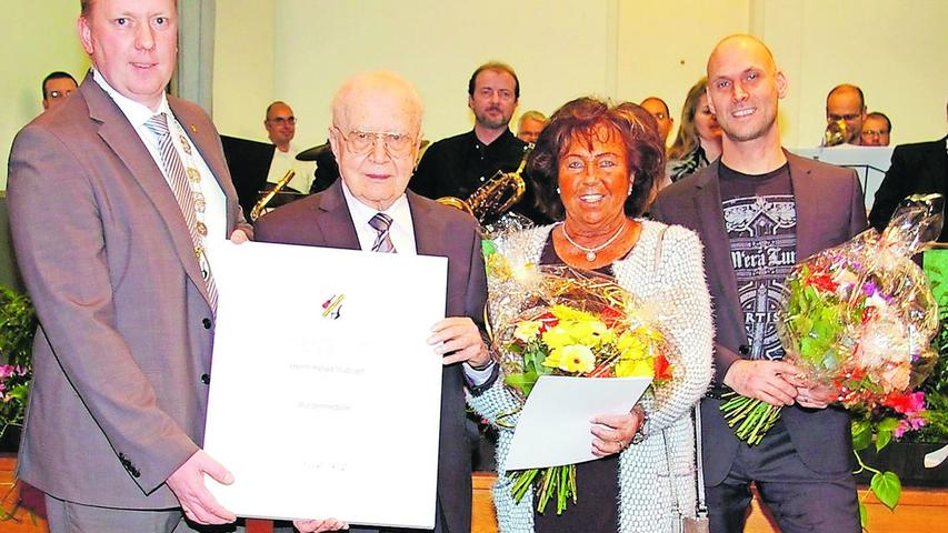 Bürgermeister Stumpf überreichte Harald Stübiger die Bürgermedaille samt Urkunde, Blumen gab es für Christl Frühwald und Andreas Haensel.