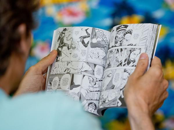 Ein Besucher des 16. Internationalen Comic-Salons liest am 19.06.2014 in  Erlangen (Bayern) ein Comic. Der Beginn des Ersten Weltkriegs vor 100 Jahren  ist thematischer Schwerpunkt des Comic-Salons. Das wichtigste Festival für  grafische Literatur im deutschsprachigen Raum hat noch bis 22. Juni geöffnet.  Foto: Daniel Karmann/dpa +++(c) dpa - Bildfunk+++