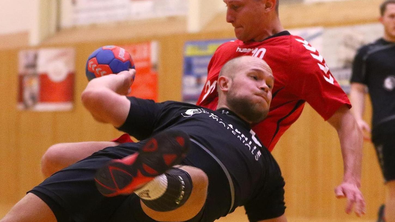 Der Zirndorfer Kim Nickl (am Ball) wirft sich akrobatisch in den Kreis, Patrick Scherbel von der SG Schwabach/Roth kann das nicht verhindern.