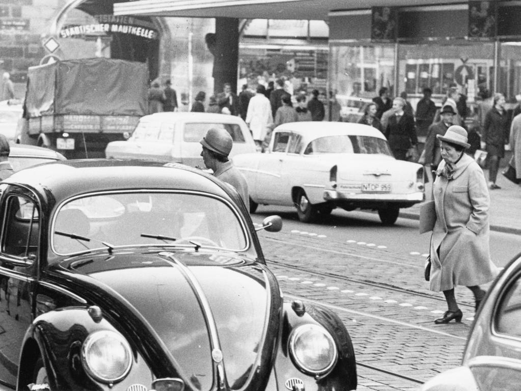 FOTO: NN / Hans Kammler, historisch; 1960er; veröff. NN 21.10.1966..MOTIV:  Verkehr; Autos, PKW; Fußgängerin, Dame mit Hut, überquert die  Fahrbahn.....KONTEXT: