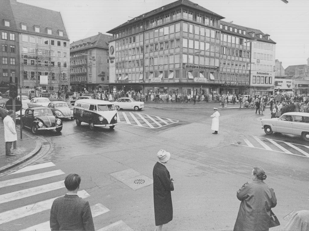FOTO: Gertrud Gerardi, veröff. 16.08.1961. Historisch; 1960er...MOTIV:  Nürnberg; Altstadt; Lorenzer Platz / Platz vor der Lorenzkirche; Kreuzung;  Verkehr. Verkehrspolizist; Verkehrsregelung; Augenblick; Fußgänger; AUtofahrer;  Polizist. Der Verkehr stockt im Gedenken an den Mauerbau in Berlin.  Gedenkminute. DDR; BRD; Geschichte...KONTEXT: