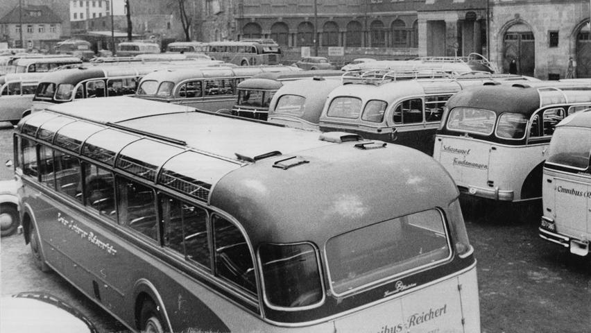 An einem verkaufsoffenen Sonntag im Jahre 1953 zog es viele Menschen in die Stadt. Während sich die Menschenmassen in den Straßen der Nürnberger Innenstadt drängten, standen auf den Parkplätzen brav die zahllosen Autobusse. Der Blick auf den Kornmarkt zeigt eine wahres Meer aus Omnibusdächern.