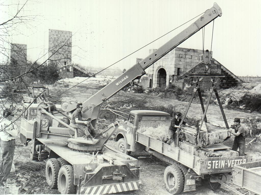 In der Nachbarschaft des niedergelegten Turms wird fleißig gearbeitet. Ein schwerer Autokran hebt die übriggebliebenen Quader auf Lastzüge. Im Hintergrund die freigelegte Anlage.