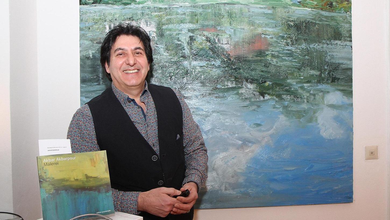 Akbar Akbarpour mit dem von Galerist Christian Fritsche verlegten Buch, das zur Ausstellung erschienen ist.