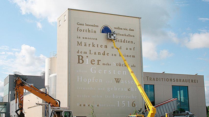 In großer Schrift wurde das Reinheitsgebot am Tucher-Gebäude angebracht. Die Arbeiter vervollständigen gerade das Logo der Brauerei.