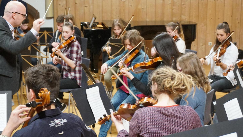 """Musiklehrer Franz Rauch dirigiert im Reitstadel das Streicherensemble """"Camerata"""" des Ostendorfer Gymnasiums."""