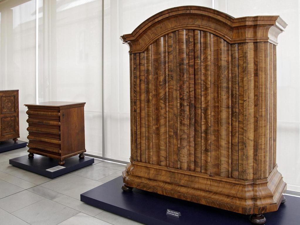 """Ein Prunkstück ist der Nürnberger """"Wellenschrank"""" aus dem 18. Jahrhundert. Und wo, verflixt nochmal, ist hier das Schloss? Es versteckt sich an der rechten Seitenwand, damit die gleichmäßigen Wellen an der Front nicht unterbrochen werden. Möbel spielten schon bei der Gründung des Germanischen Nationalmuseums eine wichtige Rolle. Allein der Bestandskatalog zu Schränken und Kommoden von 1650 bis 1800 umfasst beinahe 600 Seiten."""