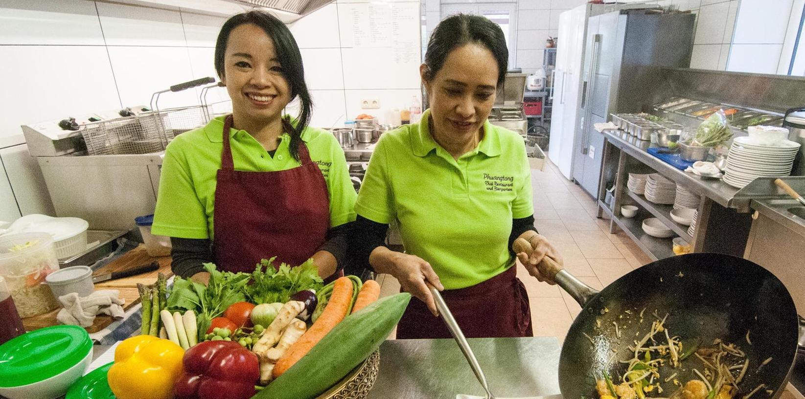 Bevor Phuangtong Zimmermann (rechts) und Suphawadee Müller (links) den Wok anheizen, muss viel frisches Gemüse klein geschnitten werden.