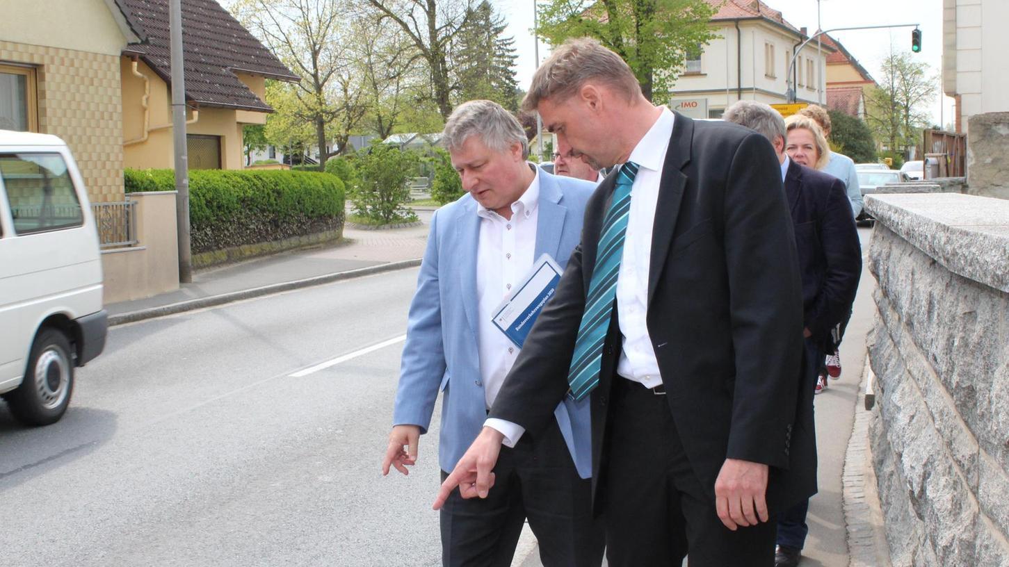 Markus Franke (r.), Sprecher der Gremsdorfer Bürgerinitiative, zeigt Martin Burkert den schmalen, lädierten Gehsteig an der Engstelle in der Ortsdurchfahrt.