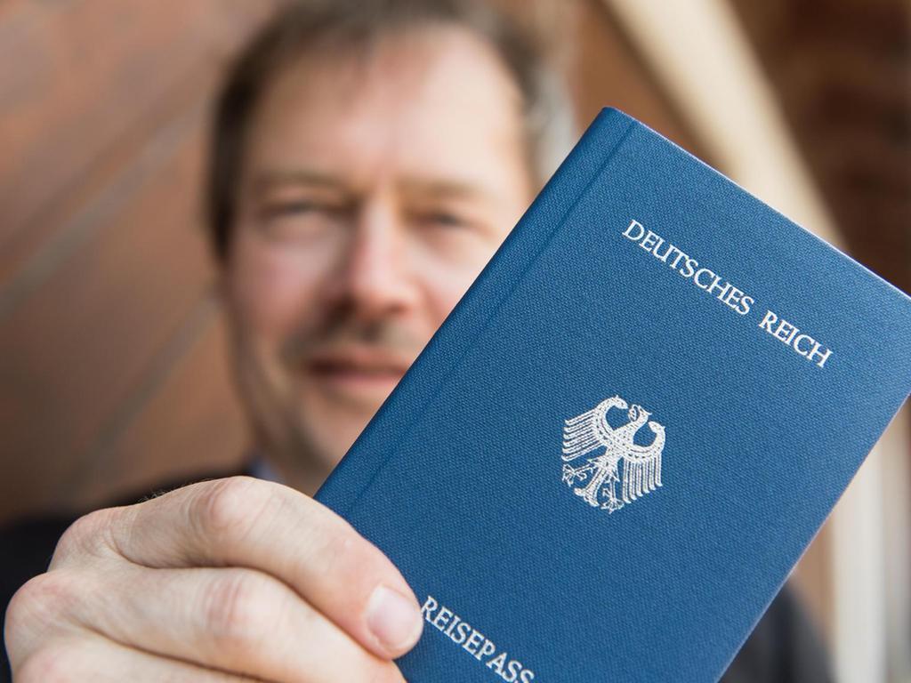 """Stolz posiert Joachim Widera mit seinem selbstgebastelten """"Reichspass"""". Die Partei des Reichsbürgers """"Deutsche Zukunft"""" hat etwa 30 aktive Mitglieder. """"Es ist Zeit für einen Systemwechsel"""", sagt er."""