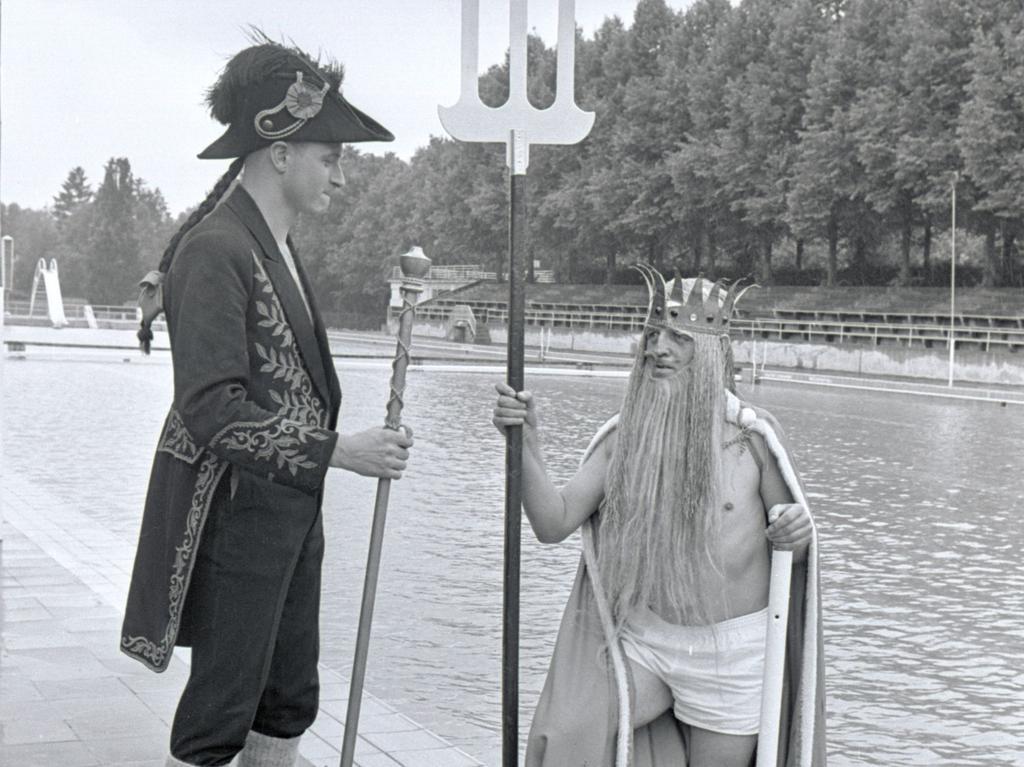 Gott Neptun steigt aus dem Wasser und wird von seinem Zeremonienmeister empfangen (links). Dann müssen die jungen Rettungsschwimmer eine lustige Prozedur über sich ergehen lassen.