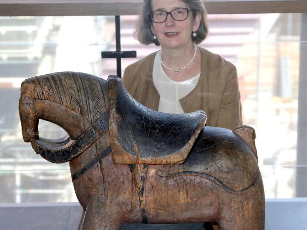 """Auf den ersten Blick scheint dieses Tierchen ein Elefant mit kräftigen Stoßzähnen zu sein. Wer sich näher heranwagt, erkennt: Es ist ein Pferd mit ziemlich kleinem Kopf, sehr, sehr dicken Beinen und viel zu kräftigem Körper. Eleganz ist das letzte, was einem dazu einfällt. Und was aus der Ferne wie mächtige Stoßzähne wirkt, sind in Wahrheit die Zügel. """"Elefantenpferd"""" nennt Claudia Selheim, die Leiterin der GNM-Sammlungen zu Volkskunde, Spielzeug und Judaica das Holztier. Dendrochronologische Untersuchungen des Holzes belegen: Das Tier wurde um das Jahr 1700 geschnitzt. """"Und zwar aus einem Stamm"""", erklärt die Fachfrau."""