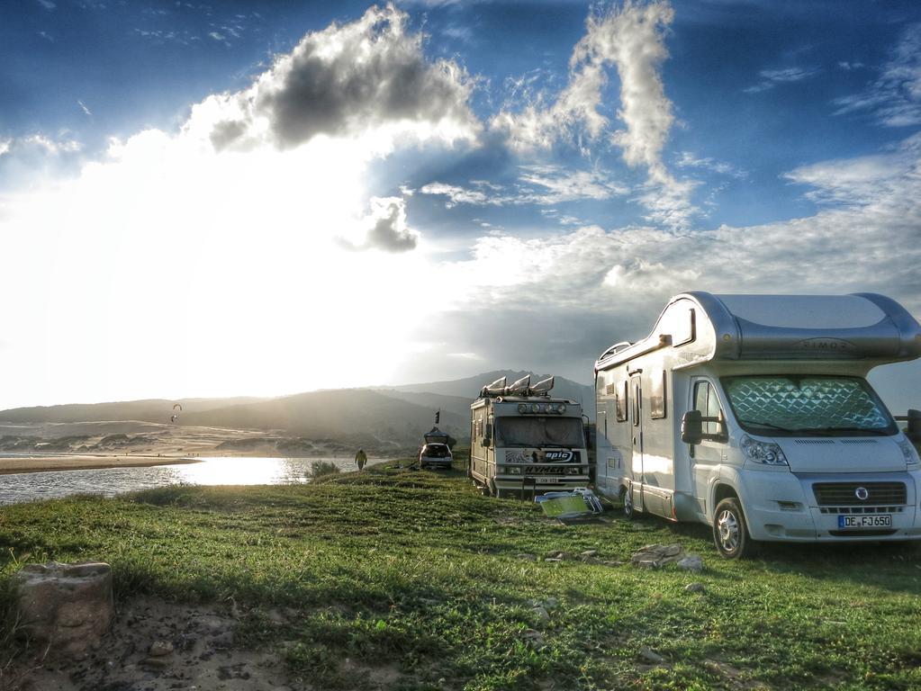 Auf einer Wiese bei Tarifa stehen unzählige Wohnmobile und Campingbusse hinter einem Kitesurfer-Strand. Kaum eine Region eignet sich so gut für eine Wohnmobil-Rundreise wie Andalusien. Doch man muss Zeit mitbringen, denn die Anreise ist lang. Dafür belohnt der Landstrich mit einer Vielfältigkeit und tollen Stellplätzen an Stränden, auf Bergen und in hübschen Städtchen.