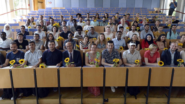 Die Teilnehmer der Sprachkurse (mit Sozialbürgermeisterin Elisabeth Preuß und FAU-Vizepräsident Günter Leugering) bei der Abschlussfeier im Hörsaal C.