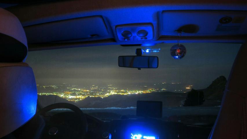 Aus der Sierra Nevada blickt man nachts durchs Wohnmobil-Cockpit auf das beleuchtete Granada herab.
