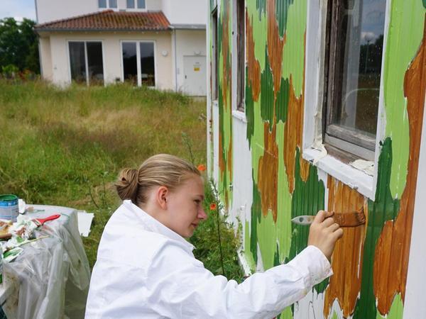 . . . seine Mitschülerin malt den Container bunt an . . .