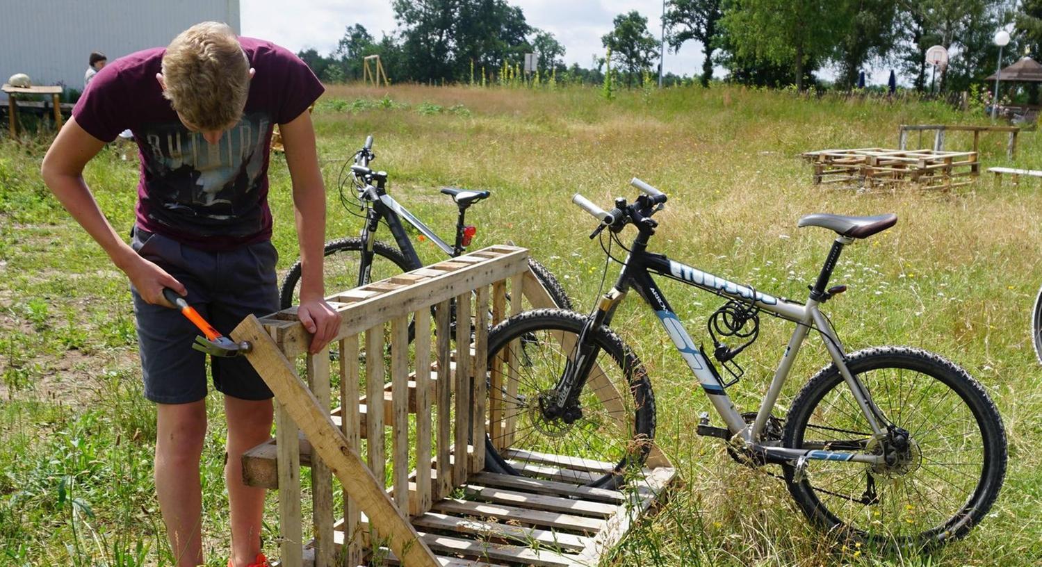 Die Schüler fahren immer mit dem Rad zum Grundstück. Für die Räder baut Tim heute einen Fahrradständer aus alten Paletten, . . .