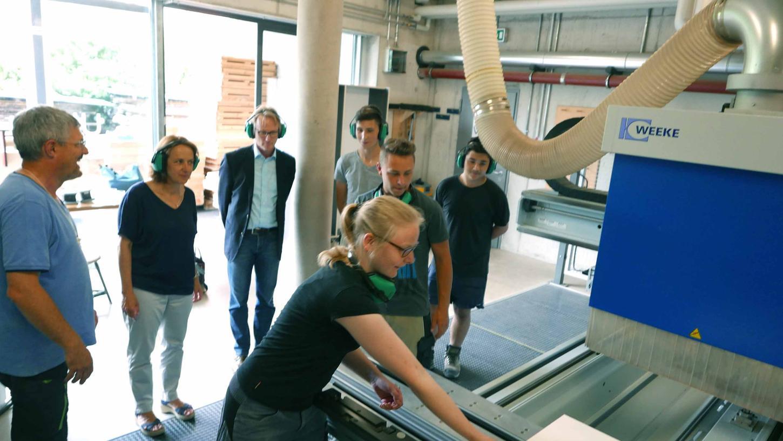 Museumsleiterin Silvia Pertschi beobachtet die Fertigung der hölzernen Wappenschilde durch Schülerinnen des Schreiner- BGJ an der Berufsschule Neustadt. Fachlehrer Thomas Medack (l.) hat dafür das computergesteuerte Programm entwickelt.