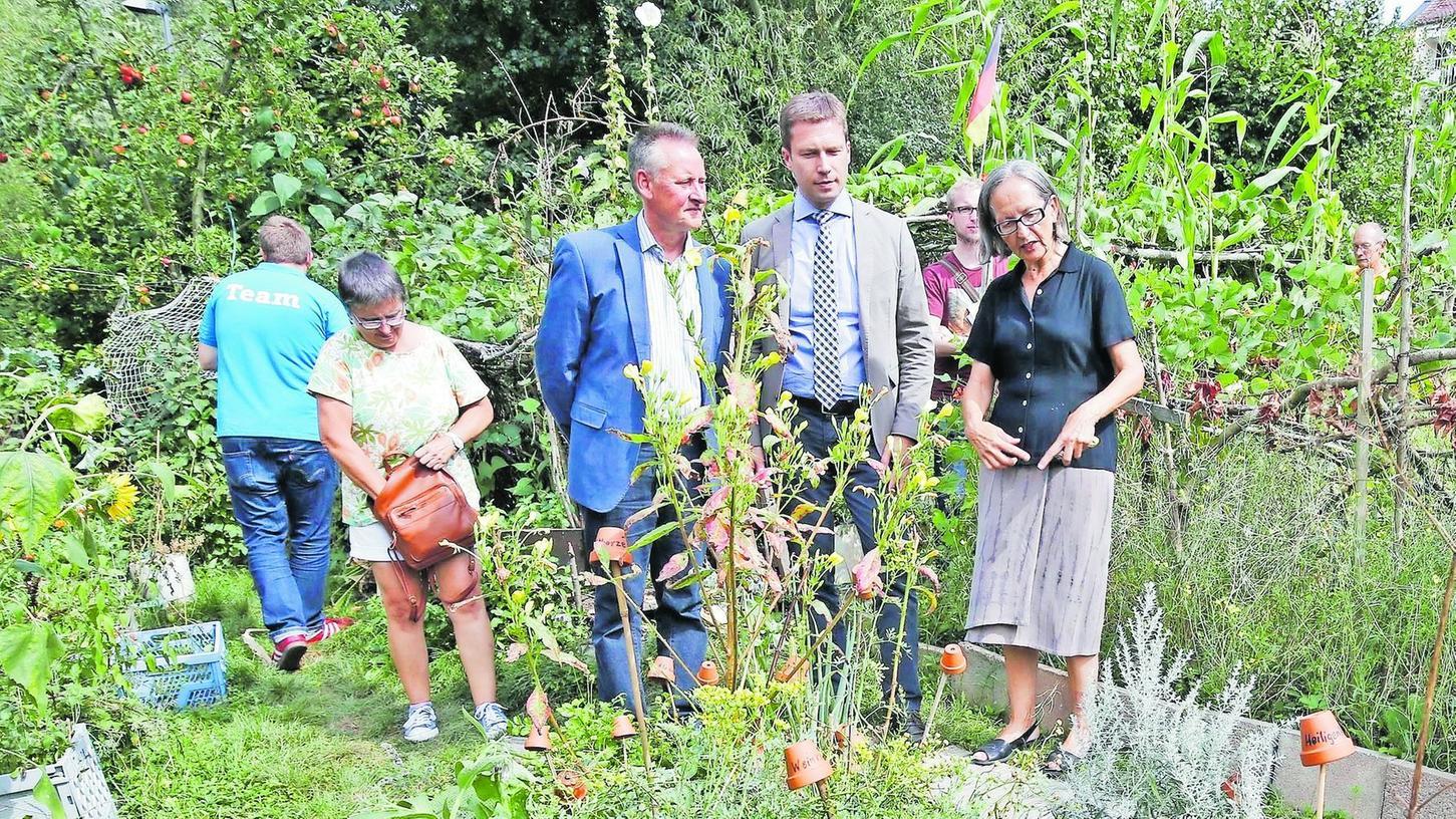 Von Helga Balletta (v. re.) lassen sich Landrat Matthias Dießl und OB Thomas Jung den Interkulturellen Garten erläutern.