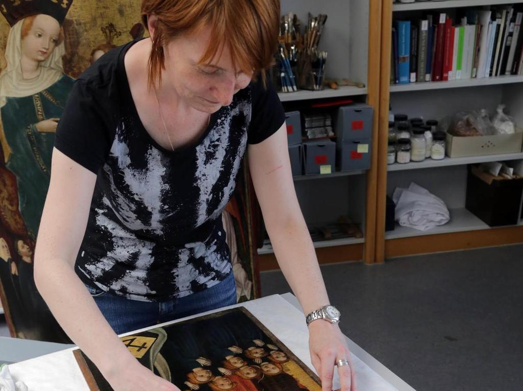 Restauratorin Margarete Juros gibt der Heiligen Ursula ihre untere Hälfte zurück. Ähnlich verfährt sie mit der Darstellung der Heiligen Barbara. Die Holztafeln aus dem 15. Jahrhundert, die zu einem Altar gehörten, wurden einst zersägt. Im Kunsthandel konnte das GNM die unteren Hälften nun erwerben und die rüde beschnittenen Teile wieder aneinanderfügen.