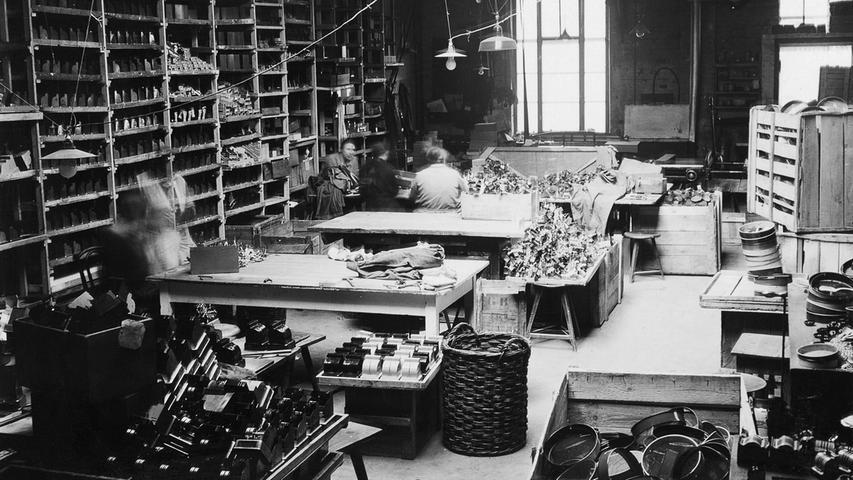 Und so produzierte der Betrieb fortan Registrierkassen und Waagen im Miniformat, die Kinder für ihre Kaufläden brauchten. Auch Spardosen und Spielzeugtelefone gehörten zum Sortiment, wie es die Firmenchronik des Unternehmens dokumentiert. Das Bild zeigt den Blick in eine Fertigungshalle, aufgenommen 1921.