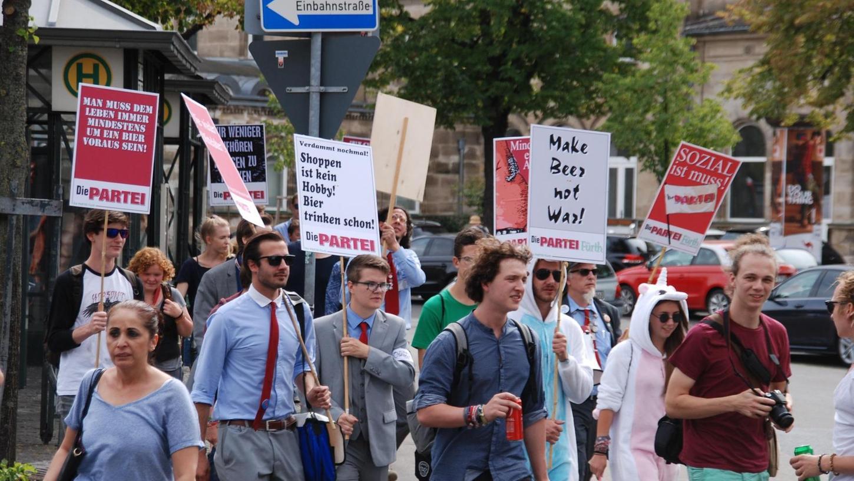 Wild entschlossen: Die Partei mit dem Fürther Kreischef Alex Kalb (rote Krawatte, Sonnenbrille) macht sich auf den Weg in die Innenstadt und gleichzeitig auf zur Bundestagswahl 2017.